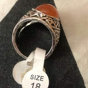 Säljer denna ringen med en orange sten i, aldrig använd och lappen är kvar. Köparen står för frakten! Kolla gärna in andra annonser!!