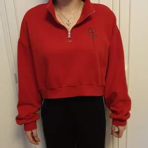 Röd långärmad tröja med dragkedja och broderad ros. Ganska tjockt tyg men väldigt kort. Storlek M. Kan skickas på posten men möts helst upp.