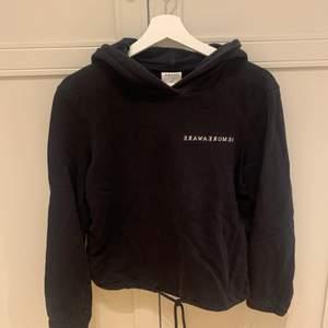 En svart hoodie i storlek XS, passar även S. Den är lite kortare med snören att knyta i midjan. Köparen betalar frakten!