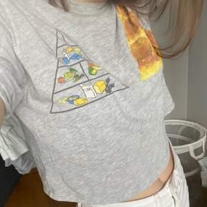 Lite croppad grå t-shirt med en liten design. Köparen står för frakt.