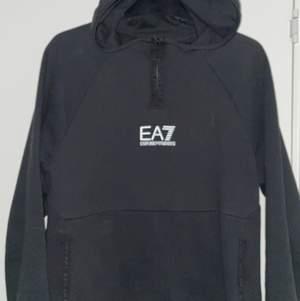 Svart EA7 hoodie i strlk L passar även M. Nypris 1100kr. Använd en gång. Reflex på märket och små EA7 logor runt hela luvan och vid magfickan med dragkedjor. Inga fläckar eller trasig någonstans. QR-kod finns! Äkta!