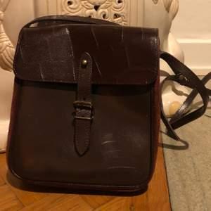 Äldre väska, köpt på second hand i brunt läder med mocka på sidan. Skada på framsidan, stängs med knäppe samt har en inre ficka.