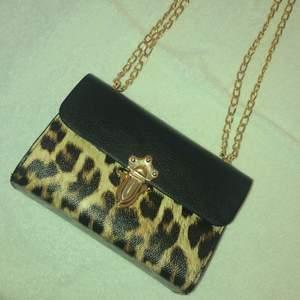 Super fin leopard väska, helt oanvänd!! Köptes för ett tag sedan men aldrig hittat ett bra tillfälle för användning. Boxformad med printat leopard mönster och gulddetaljer. Gysterbar axelkedja.