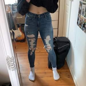 Ripped tighta blåa högmidjade jeans från American Eagle, väldigt stretchiga och sköna, sitter fint och bra längd. Storlek 2 (US) som är ca 38 (EU). Bra skick. Pris: 170kr inklusive frakt