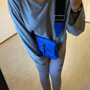 Säljer min Donna Donna väska som aldrig är använda och prislappen är kvar. Den blåa färgen är otroligt snygg och passar perfekt nu till sommaren. Det tjocka bandet gör väskan extra snygg och detaljerna. Väskan kostade 400kr.  Man kan självklart byta ut bandet också.🤩