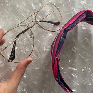 Ett par glasögon med vanlig glass som fraktas i bubbelplast med ett hårband som följer med