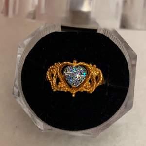 En guldig ring med ett blått hjärta som detalj.                              Lådan ingår inte!                                                                      Frakt tillkommer!