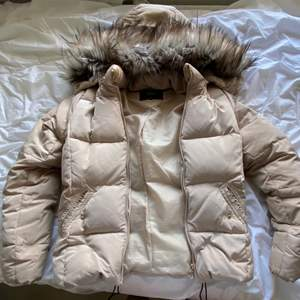 Denna beigea dunjacka var köpt runt 2019 för 1000kr. Den är i otroligt bra skick då den var bara använd en vinter. Pälsen ser perfekt ut, det finns inte heller några slitna märken runtomkring på utsidan eller insidan. Jackan håller väldigt bra och är riktigt varm och skön att ha på sig.