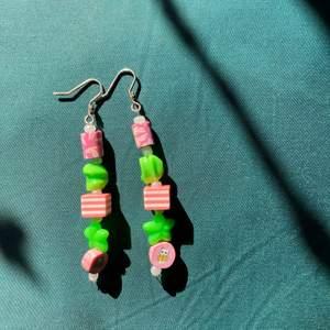 Jättegulliga, handgjorda örhängen med rosa och gröna pärlor i plast. Pärlan längst ner har ett kattmotiv och kroken en liten blomma. 8cm långa, inte alls tunga.