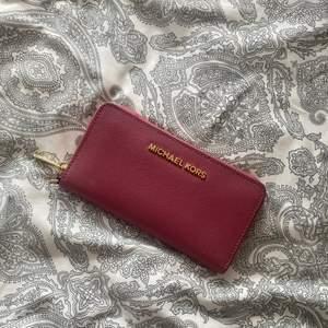 Fin rosa plånbok från Michael kors! Äkta såklart. Köptes på michael kors butiken i stockholm för ca två år sedan för 200k0kr. Den har en liten sminkfläck som syns tydligare på sista bilden men går såklart att ta bort, jag har bara inte orkat.