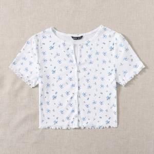 Säljer en vit tröja från SHEIN med blåa blommor och knappar. Första bilden är lånad. Tröjan är aldrig använd, alltså i nyskick. Köparen står för frakten