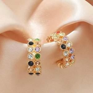 Helt nya guldiga örhängen med stenar i olika färger. Köparen står för frakten (12kr)!