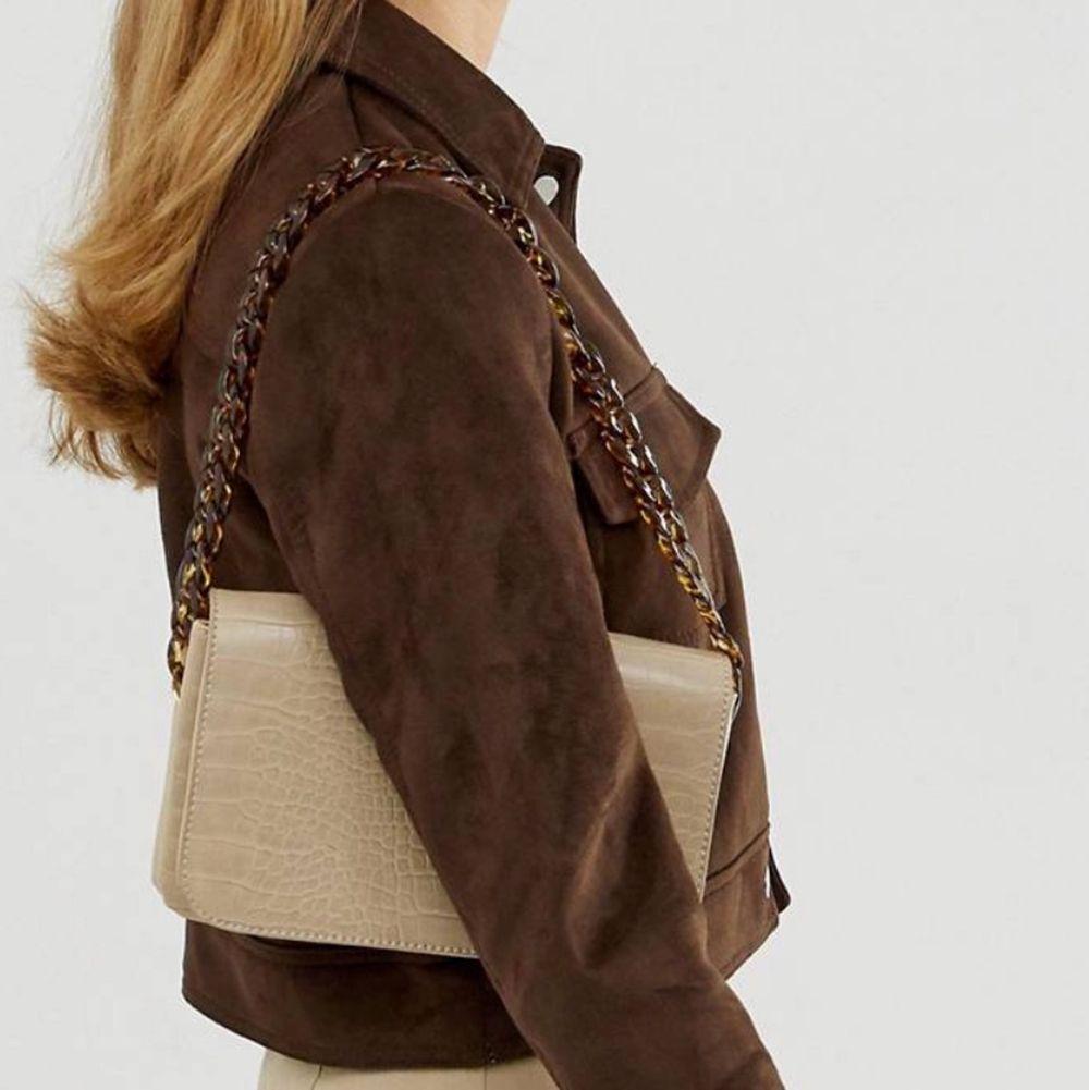 Beige väska från Asos med krokodilsskinnsimitation. Använd ett fåtal gånger men är i nyskick! Pris kan diskuteras! :) . Accessoarer.
