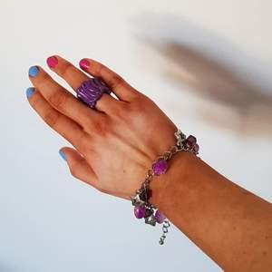 Superfint armband med lila berlocker/stenar/dekorationer, silverfärgat. Okänt märke. Aldrig använt så inga defekter.