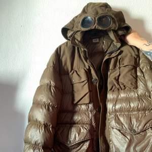 Trendig CP company goggles jacka i färgen brun, en  glansig puffer i mix med tyg med glasögon i luvan.  Nypris ligger på över 3000kr.