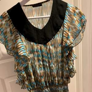 Jättefin volangig blus med tiedye färger. Från USA, köpt för några år sen men tyvärr kom inte till så mycket användning. Jättebra skick och fin för sommaren/ hösten med en tröja under.