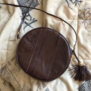 Fejk ormskinnsväska med tassel. Fint skick, någon repa som ni kan se på 3e bilden