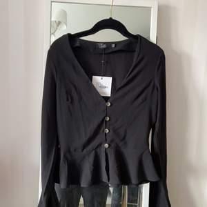 En v-ringad blus med knappar i fram, volanger längst ner på blusen och vid ärmarna. Har aldrig använt. Frakt ingår