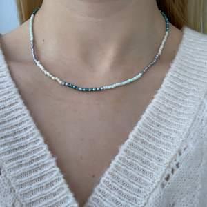 Flerfärgat pärlhalsband med små pärlor🦋🤍🥰💙⭐️💫🥳🍬💞 halsbandet försluts med lås och tråden är elastisk