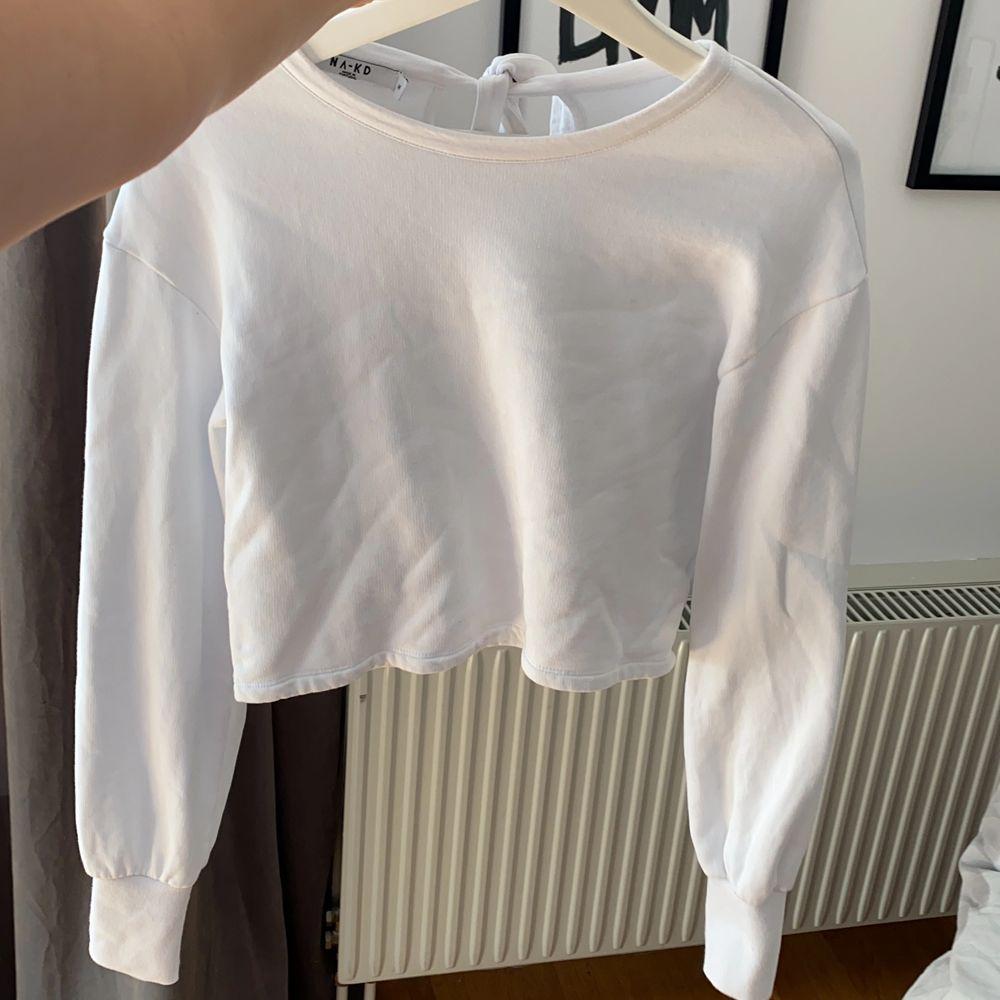 Vit tröja från NAKD som är kort i modellen, aldrig använd eftersom att jag föredrar lång modell. Knytes bak i nacken vilket är en fin detalj. snygga till högmidjade byxor! . Tröjor & Koftor.