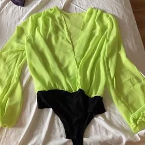 Neon grön body, ALDRIG använd. Nypris 300kr, frakten är inräknat i priset.