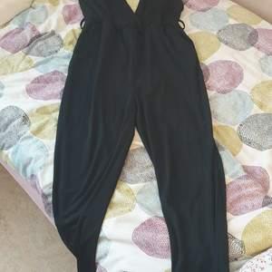 En svart byxdress med öppen rygg och band som du fäster vid nacken. Perfekt för en kväll ute med tjejerna eller en dejt. Funkar också för fester
