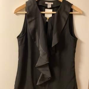 Svart ärmlös blus med en framsida av krås volang i storlek 38. Aldrig använd, köpt för 249kr på H&M! Säljes för 100kr inklusive frakt på 22kr.