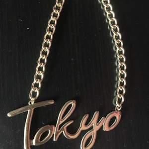Halsband i Guld med texten Tokyo. Köpare står för frakt.