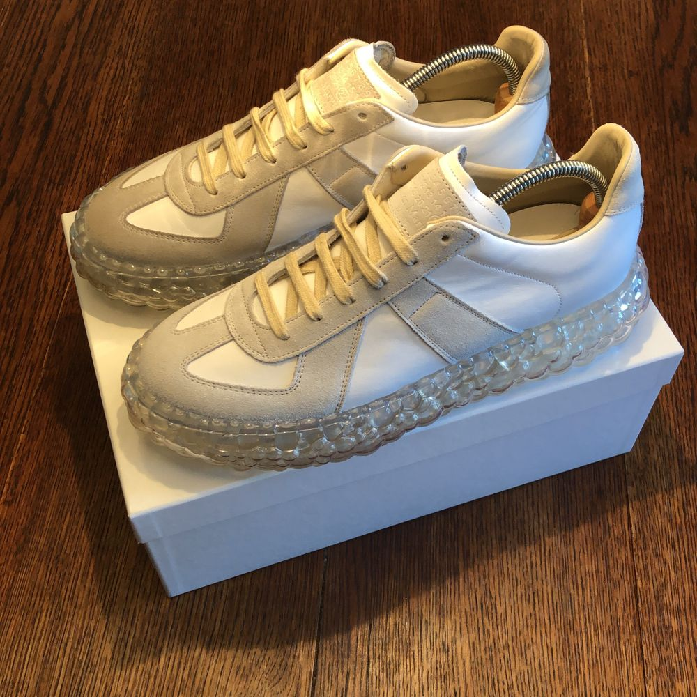 """Den klassiska modellen """"Maison Margiela Replica"""", fast med en bubbelsula. Ett par av de absolut coolaste skorna, som det franska modehuset tagit fram. Unikt utseende som drar blickar till sig. Mod. S37WS0503-White. Enbart använda två ggr av mig inomhus, dock är den högra skon något mörkare än den vänstra pga. prövad av andra kunder. Försvinner när du börjar använda dem. Nypris:6295kr . Skor."""