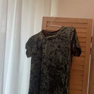 En grön T-shirt med grov sammet. Använd ett fåtal gånger, tre ca. Storlek XS. Köpt för 200kr .