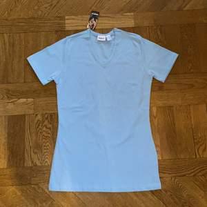 """Helt ny snygg och trendig ljusblå pastell t-shirt.💙 Nyskick/mycket bra skick då den endast är testad och lappen fortfarande är på. Storlek 34/36, på 3dje bilden ser ni hur den sitter på mig som är en XS/S. Material 95% bomull 5% elastane. Dm vid intresse/frågor/fler bilder.❣️ (Det kan du göra här under för det står """"kontakta"""") Avhämtning på Södermalm eller frakt till självkostnadspris.:)"""
