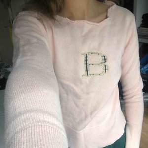 Gratis frakt Äkta Burberry tröja! Urfin ljusrosa färg. Stickad och med ett broderat B med deras signatur mönster -  XS/S