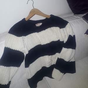 En mysig stickad tröja ifrån  dobber. Den är randig  i vit och mörkblå.