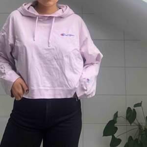 En skitsnygg croppad hoodie från märket Champion. Det är en lila/rosa färg och rätt lös i storleken så passar en m också!