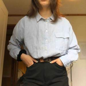 En blå och vit randig skjorta från Kappahl i storlek L men passar mig som har S om man vill ha lite oversize är den perfekt för S. Den är avklippt nedtill (se bild 3). Frakten står köparen för