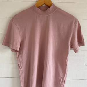 En t-shirt från & Other Stories i en rosa/mauve ton. Har en turtle neck-krage. Originalpris: 300 kr