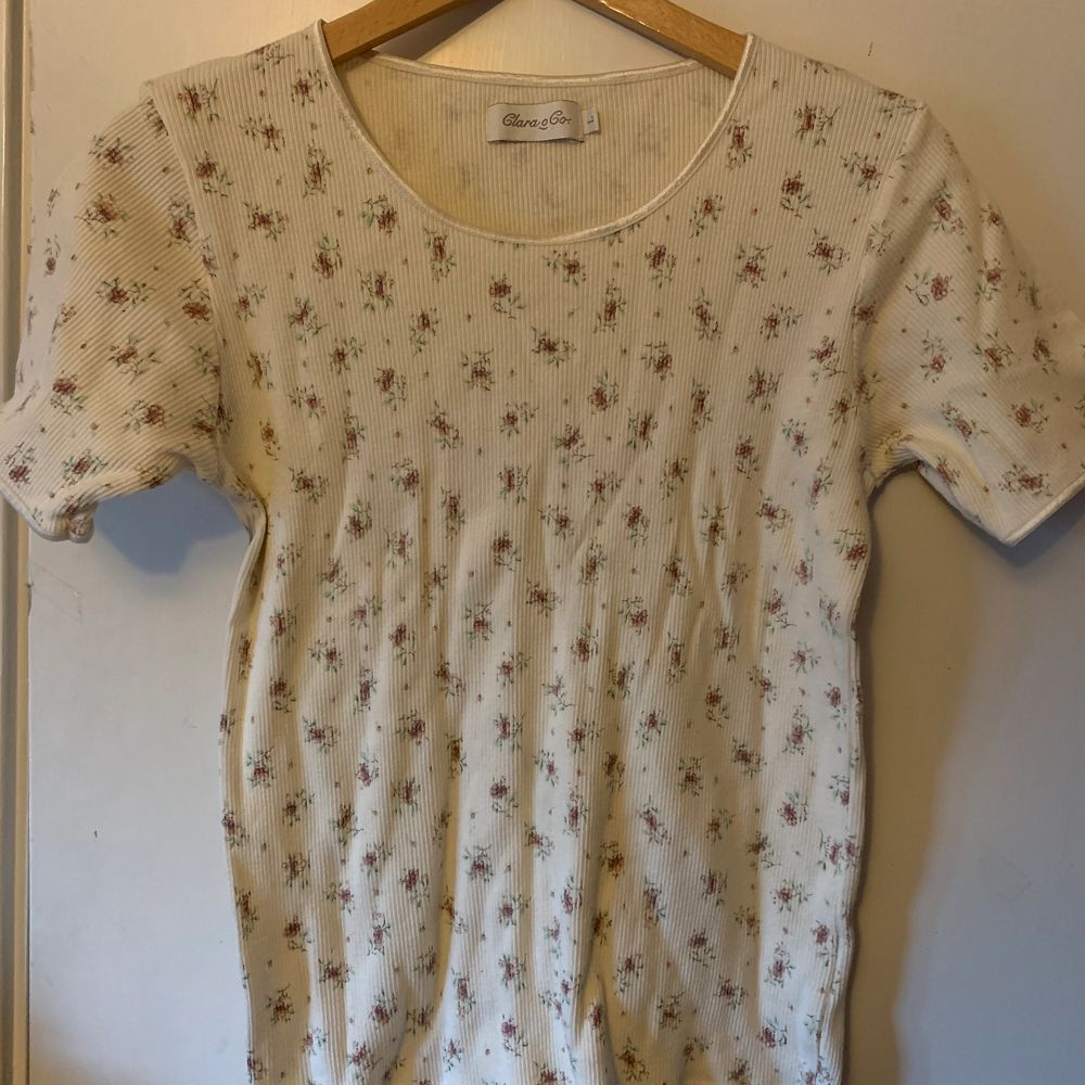 Vit ribbad tröja med små blommor på. Fint skick utan någon fläck och den visas på en M. . T-shirts.
