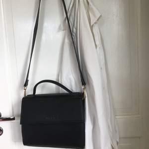 Väska i svart fakeläder från NA-KD med avtagbart axelband. Toppenskick då den aldrig har använts! Nypris 499