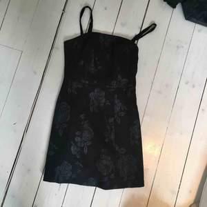 Jättejättefin liten svart klänning från Urban Outfitters. Blommor på som också är i svart men lite glansigare material, smala axelband. Storlek XS och aldrig använt. Köpt för ca 700 kr förra året