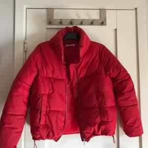 En röd jacka med puffigt material, super snygg på. Finns band man kan dra åt längst ner på jackan ifall man önskas tajta till den.