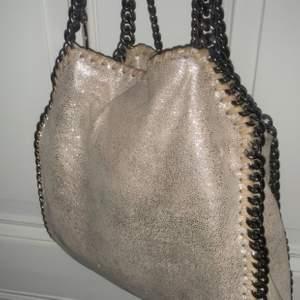 Intresse koll säljer endast vid bra bud!! Säljer min älskade Stella väska i modelen mini falabella tote. Väskan är begie och glittrig, unik. Köpt för ca 4månader sen sparsamt använd(bild 1&3 tagen med blixt) På marknaden kostar väskan ca 7000kr-8000kr. Buda i komentarna eller privat💕