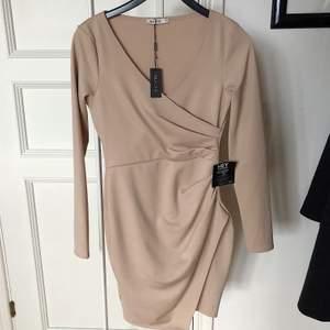 Long sleeve wrap dress i storlek xs från Nelly. Klänning är aldrig använd och har lapparna kvar. Bild nr 3 visar hur klänning sitter på. Modellen på bild nr 3 bär storlek xs