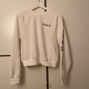 Vit sweatshirt med snyggt tryck på ryggen, använd en gång, lite croppad