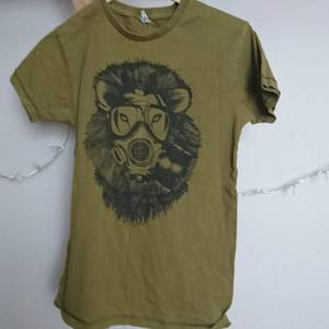 En olivgrön T-shirt med ett lejon med gasmask. Står XS men funkar upp till liten M. Köparen står för frakten.