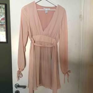 Puderrosa klänning från Nelly 🌸 Använd en gång endast, söt knytning att ha fram eller bak, även i ärmslut🎀 Köparen står för frakt