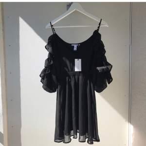 Så snygg svart klänning i chiffong med volanger och öppna armar. Aldrig använd med tags kvar. Passa på att fynda till billigt pris! Passar även S.