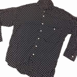 Helt ny skjort från pop med möster utav små vita prickar i det mörkblåa tyget som är utav ett tunnare rayon tyg (silke)  Skjortan kortare sydd i stilen.