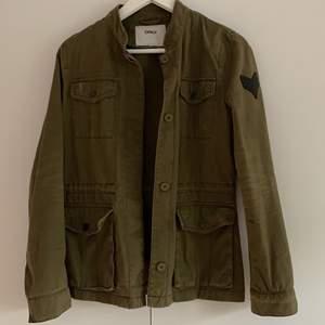 Mörk grön militär jacka, med mycket fina detaljer. Super bra skick. (Skulle säga att den är stpr i storleken, ungefär en S)