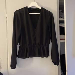 En jättefin svart blus från Gina Tricot! Den är väldigt tunn, men inte så genomskinlig när den väl sitter på. Storlek S, kan absolut passa en XS också. Det är som en stor volang längst ner, jättefint! Väldigt fint skick då den är använd väldigt få gånger🤍