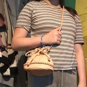 Gullig beige sidoväska med en fläta som detalj och metall detaljer på axelbanden. Öppnar och stänger den genom att knyta snöret som syns på bilden. Insidan är fläckfri. Kan mötas upp i Stockholm eller posta. Frakt 44kr. Meddela mig om eventuella frågor:)